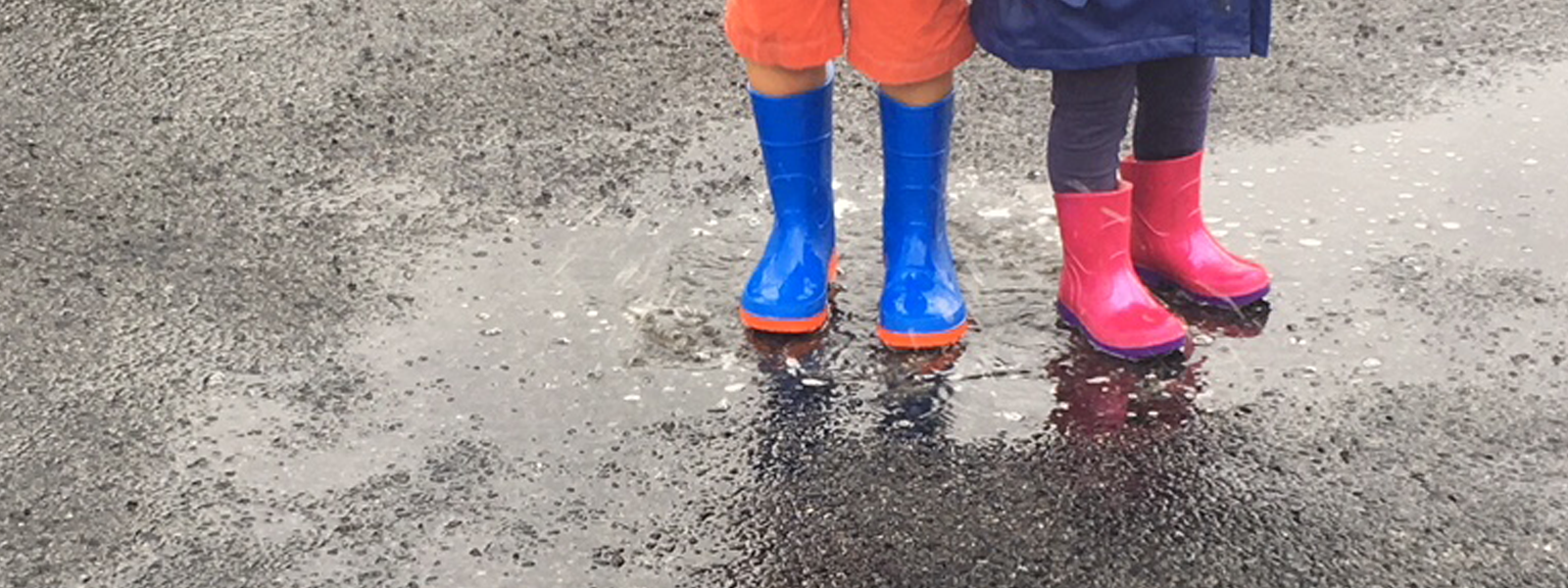 Two children in gumboots standing in a puddle.