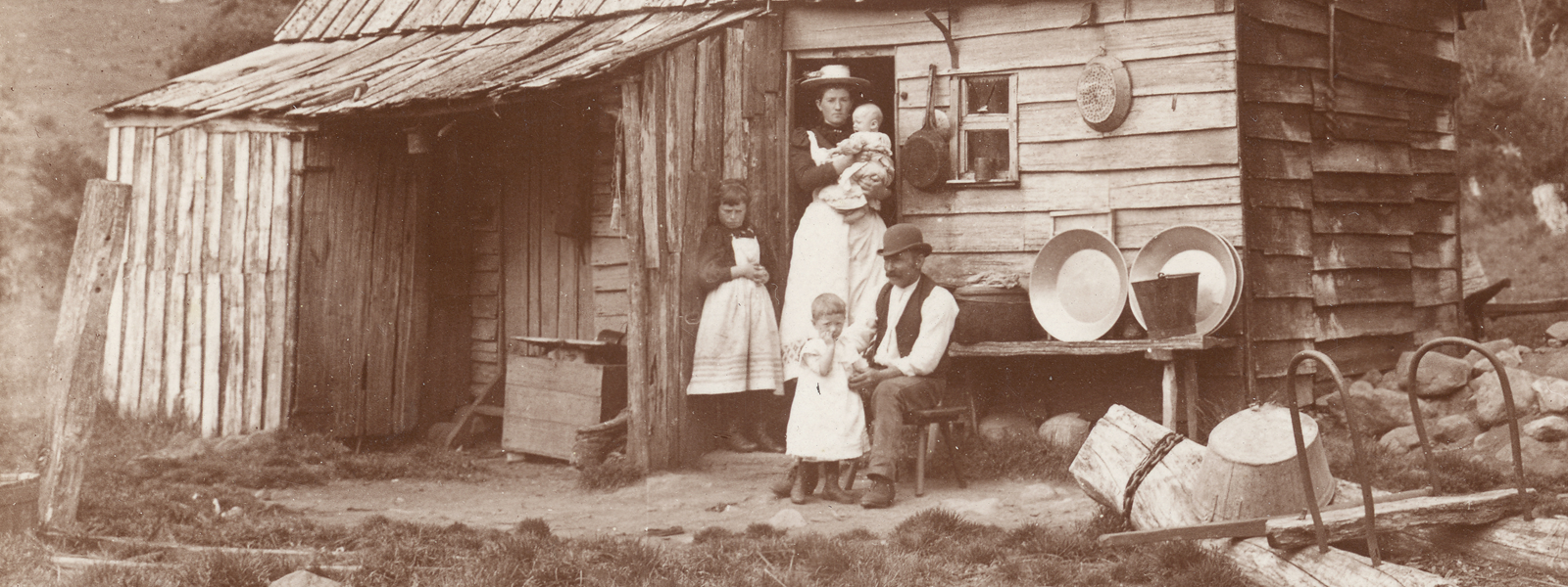 Sepia photo from the 1800s of a family outside a hut.