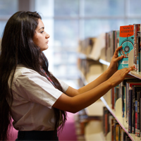 girl picking up book from a shelf